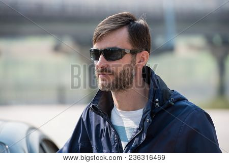 Portrait Of A Bearded Man Wearing Sunglasses In A Park. Age Of Forty Years.