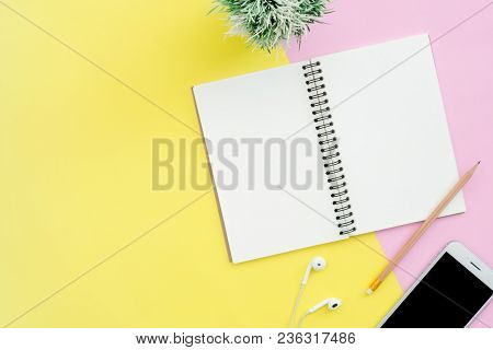 Creative Flat Lay Photo Of Workspace Desk. Top View Office Desk With Notebooks, Plant, Mock Up Phone