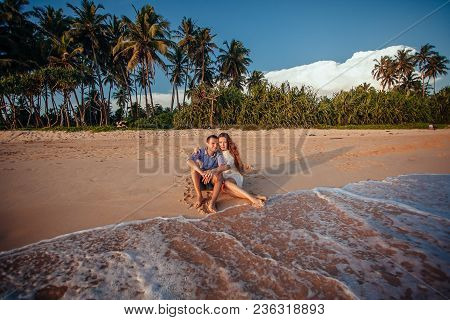 Happy Romantic Couple Sitting On Tropical Beach On Palm Trees Background, Hugging Each Other And Enj