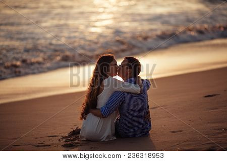 Silhouette Of Happy Romantic Couple Kissing On Tropical Beach, Hugging Each Other And Enjoy Sunset.