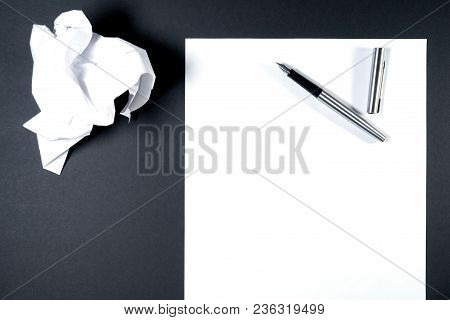 On A White Sheet Of Paper Is A Pen, Next To The Sheet