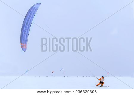 Skier  With Kite On Free Ride. Competitions On Snow Kite