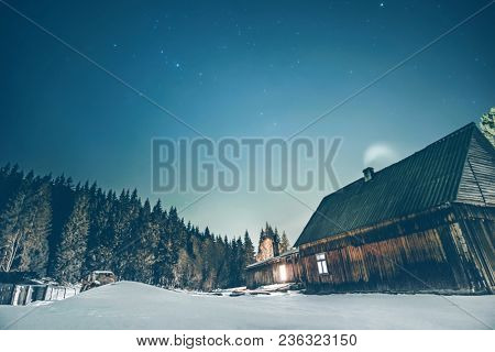 Rural wooden cottage in the mountains with windows glowing in the dark at winter night. Wooden hut on hill moutains.