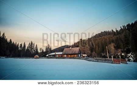 Rural wooden cottage in the mountains in evening. Wooden hut on hill moutains with old fence