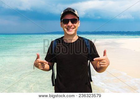 Casual Man Pointing With Both Hands To His Blank Gdark Brown T-shirt On The Background Of Beautiful