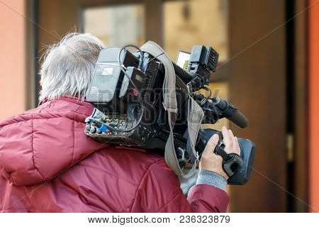 Cameraman Using  Professional Camcorder In The Street