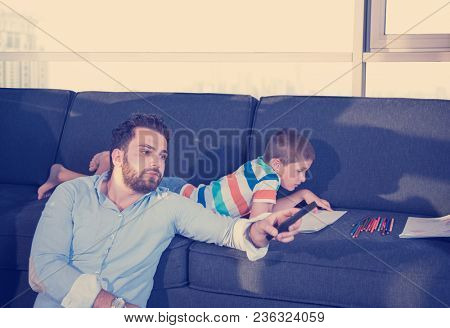 Happy Young Family Playing Together on sofa at home using a tablet and a children's drawing set
