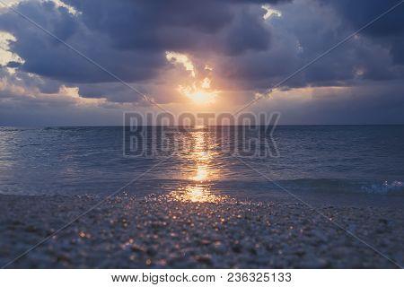 Evening Sunset On The Sea, . Purple Cloud In Orange Sky. Small Sun Look Far Away And Getting Dark. L