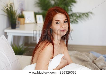 Joyful Young Woman With Ginger Hair, Freckles And Nude Shoulders Sitting On Bed, Wrapped In Blanket,