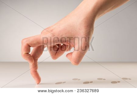 Female fingers walking on white surface with footsteps behind it