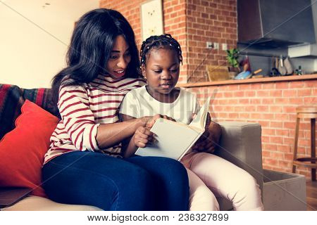 African mother helping her daughter in doing her homework