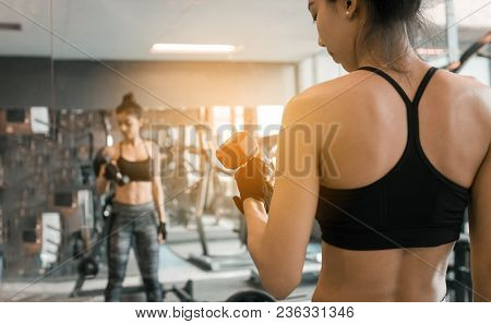 Rear View Of Asian Women Lifting A Dumbbell.