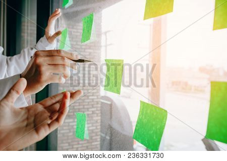 Business Team With Glass Board Room Pointing Ideas On Adhesive Notes Working Together.