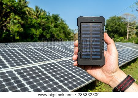 Poverbank In Hand On The Background Of Large Solar Street Standing Among The Trees. Mobile Power Ban