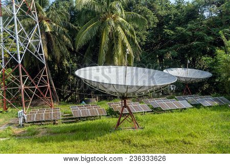 Modern Satellite Dish And Solar Panels In The Jungle Forest. Satellite Dish, Satellite Antenna, Sate