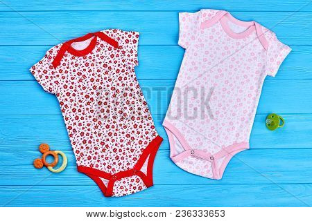 Set Of Baby-girl Cotton Bodysuits. Top View Of Two Cotton Bodysuits And Accessories For Newborn Girl