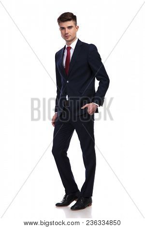 confident young businessman wearing a navy suit and a red tie, standing and posing with hand in pocket on white background, full body picture