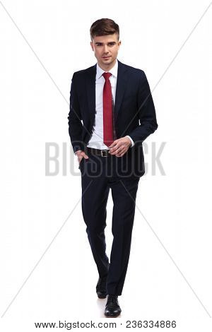 handsome businessman with hand in pocket stepping forward. He wears a navy suit and a red tie while standing on white background, full body picture
