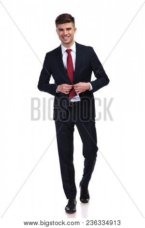 laughing businessman buttoning his navy suit and stepping forward while standing on white background, full body picture