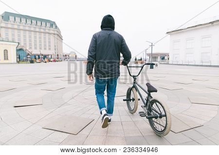 A Spine Of A Young Man Walking Around The City With A Bmx Bike. Walk With A Bike. A Cyclist Travels