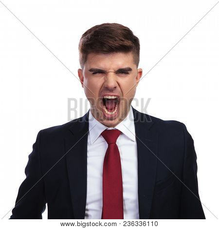 portrait of angry businessman yelling at his employees, on white background. He wears a navy coloured suit and a red tie