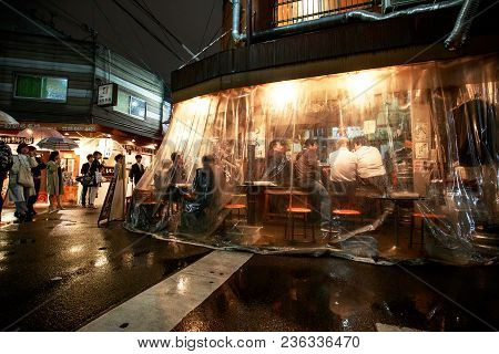 Osaka, Japan - April 14, 2018: Customers Drink In A Corner Bar Sheltered From The Wind And Rain By A