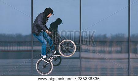 Bmx Freestyle. Stylish Man Doing Tricks On Bmx Against A Dark Shop Window. Street Culture.