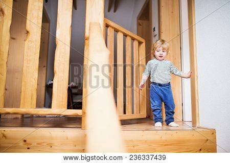 Little Toddler Boy Standing On The Top Of The Stairs. Domestic Accident. Dangerous Situation At Home