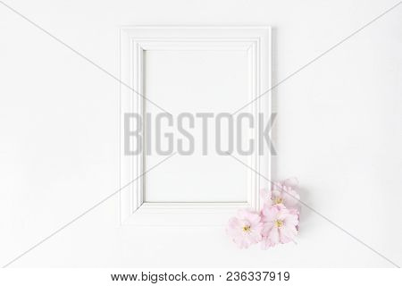 White Blank Wooden Picture Frame Mockup With Pink Japanese Cherry Blossoms Lying On The White Table.