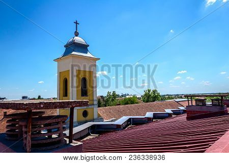 View On The Church Steeple With Metal Roof, Long City Street Is Below.