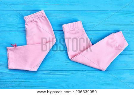 High Quality Cotton Breeches For Baby. Cotton Spring Or Summer Pants For Infant Girls Folded On Wood