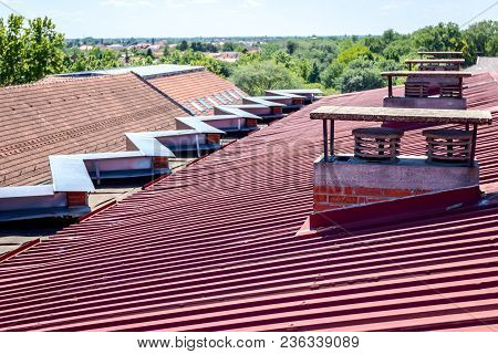 Chimney Made Of Bricks For Heating And Ventilation On The Colored Corrugated Metal Roof.