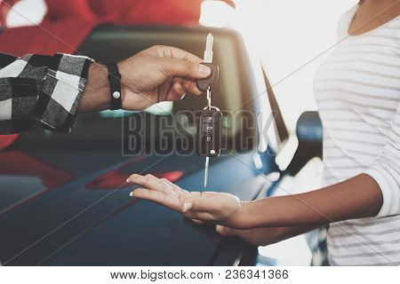 Close Up Man Is Giving Keys To Woman. African American Family At Car Dealership. Father, Mother And