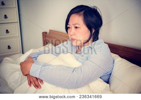 An upset woman pondering in bed