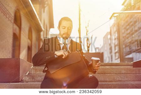 Young businessman with coffee mug to go and briefcase on the go in the city