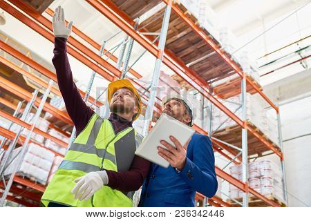 Low Angle Portrait Of Warehouse Manager Holding Clipboard Talking To Worker Wearing Hardhat And Refl