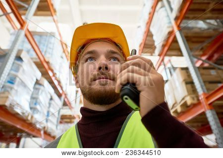 Close Up Portrait Of Young Man Wearing Hardhat And Reflective Jacket Speaking By Walkie-talkie Stand