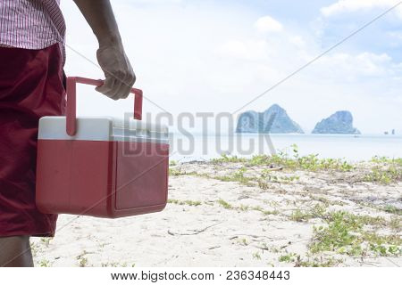 Hand  Of Man Red Ice Box  With Background The Beach And Island View.