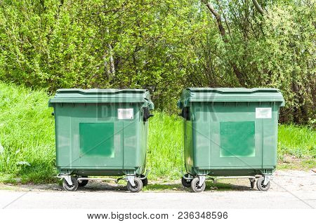 Two New Green Garbage Dumpster Cans On The Street