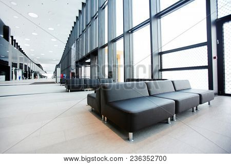 Long aisle inside modern airport lounge with several black leather seats along