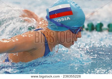 ST. PETERSBURG, RUSSIA - APRIL 11, 2018: Girl competes in 100m butterfly swimming during All-Russian Swimming Competitions Merry Dolphin. The competitions was founded in 1965