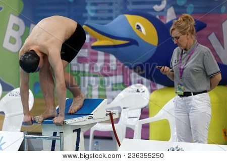 ST. PETERSBURG, RUSSIA - APRIL 11, 2018: Man on start of 100m butterfly swimming during All-Russian Swimming Competitions Merry Dolphin. The competitions was founded in 1965