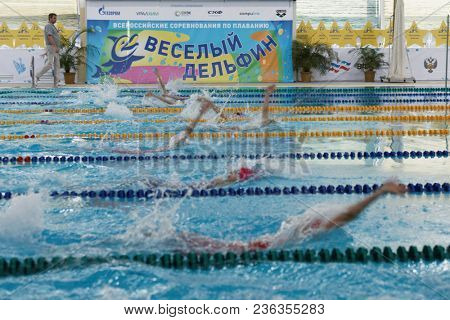ST. PETERSBURG, RUSSIA - APRIL 11, 2018: Girls compete in 100m backstroke swimming during All-Russian Swimming Competitions Merry Dolphin. The competitions was founded in 1965
