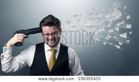 Handsome businessman shoots his head with gun and documents coming out from his head
