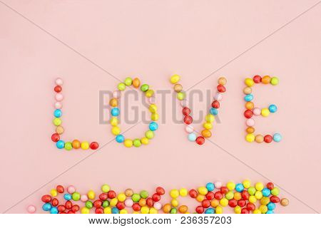 The Inscription Love Of Colorful Candies On A Pink Background