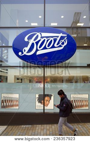 Bracknell, England - April 16, 2018: A Pedestrian Passes By The Window Display Of The Boots Retail S