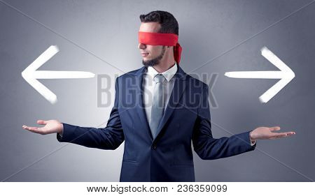 Covered eye businessman choosing between two directions