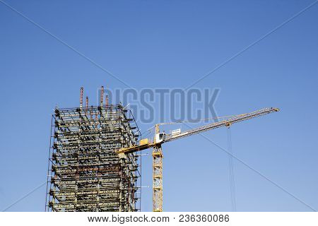 Big Yellow Construction Crane And The Skeleton Of An Unfinished Skyscraper  The Background Of Blue S