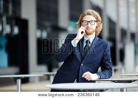 Serious businessman with smartphone making call to one of his clients or colleagues in airport