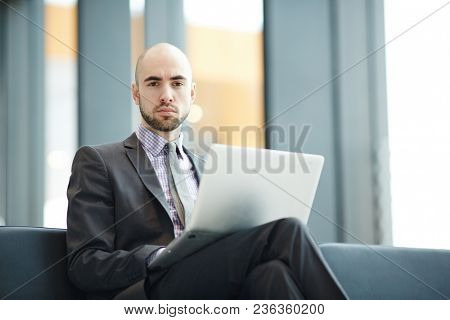 Serious young businessman in elegant suit looking at camera while waiting for his flight in airport lobby